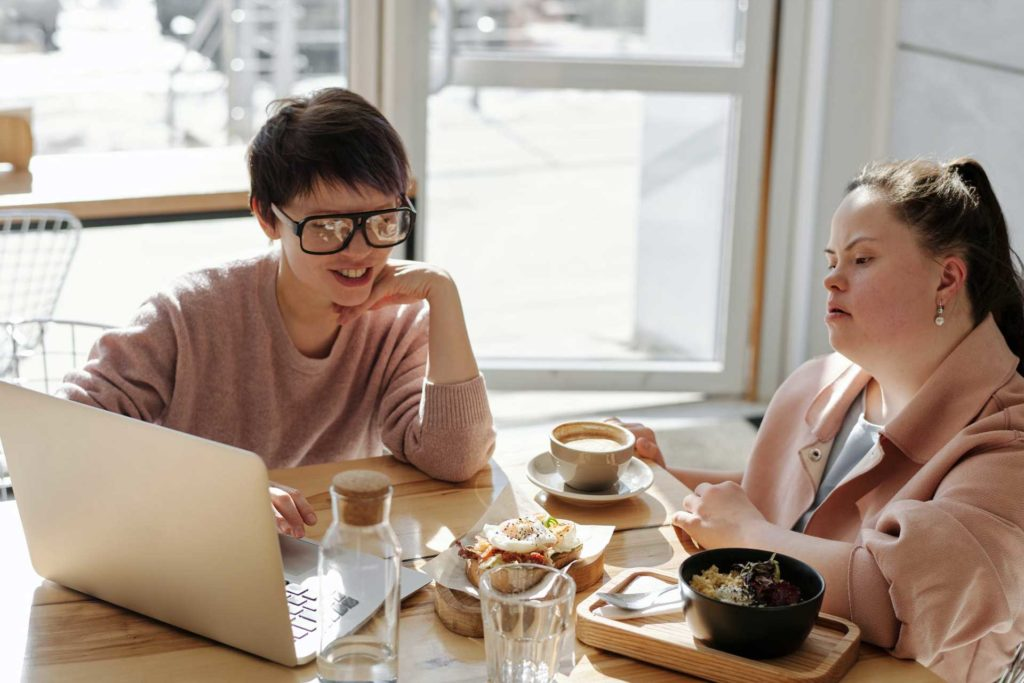 Two young women with disabilities sitting down at a cafe having a business meeting.