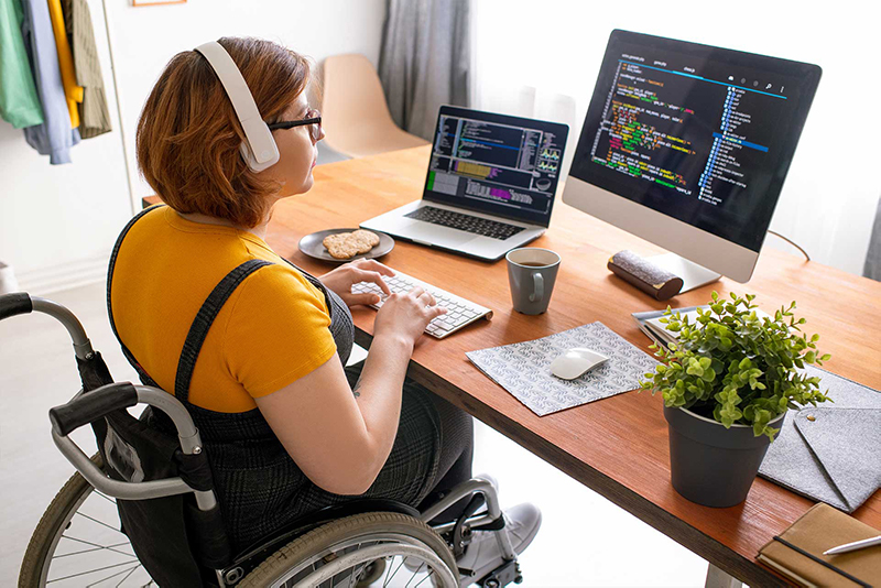 Woman in wheel chair coding in from of a computer