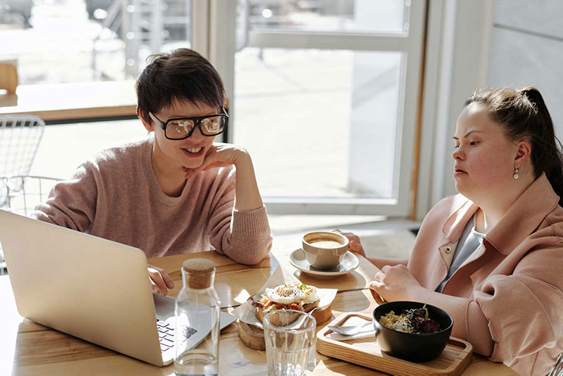 Two women younger women with disabilities talking over lunch looking at a computer