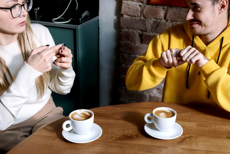 Two people using Sign Language at coffee shop