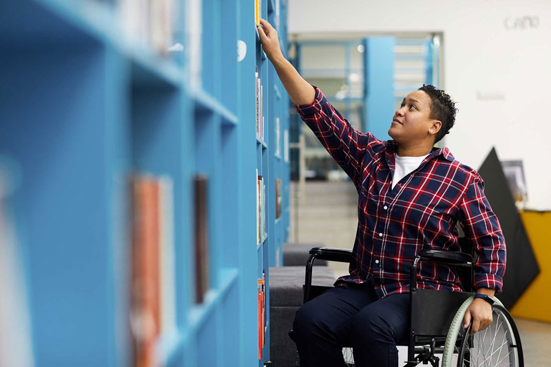 Woman with disability at library getting books