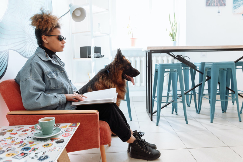 Visually Impaired Woman reading braille with Seeing Eye dog next to her sitting down