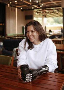 Smiling woman with prosthetic arm having coffee at a coffee shop